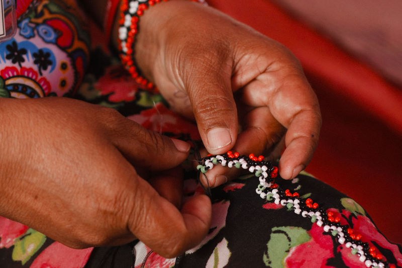 Cropped hands of woman sewing beads on fabric