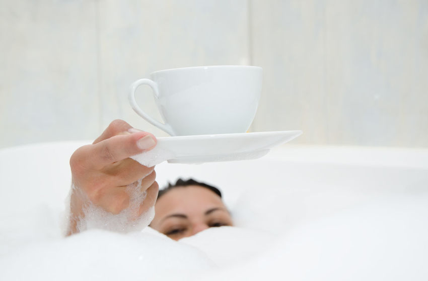 Woman Lying in a Bathtub with Foam and Holding a Cup of Coffee Adult Humor Looking At Camera Woman Bathroom Bathtub Close-up Color Concept Cup Of Coffee Day Foam Focus In Foreground Hidden Holding Holding Up Human Body Part Human Hand Indoors  Lifestyles Lying Down One Person One Woman Only People Real People