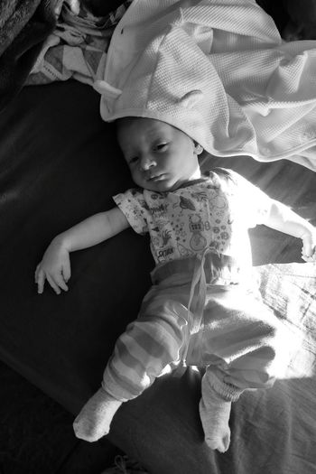 High angle view of cute baby sleeping on bed at home