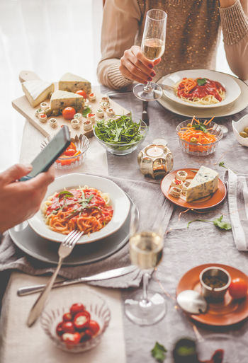 Food And Drink Food Table Plate Glass Freshness Drink Indoors  Human Hand Hand High Angle View Refreshment Household Equipment Vegetable Real People Drinking Glass Ready-to-eat Holding Meal Telephone Smart Phone Champagne Socializing Lunch Vertical