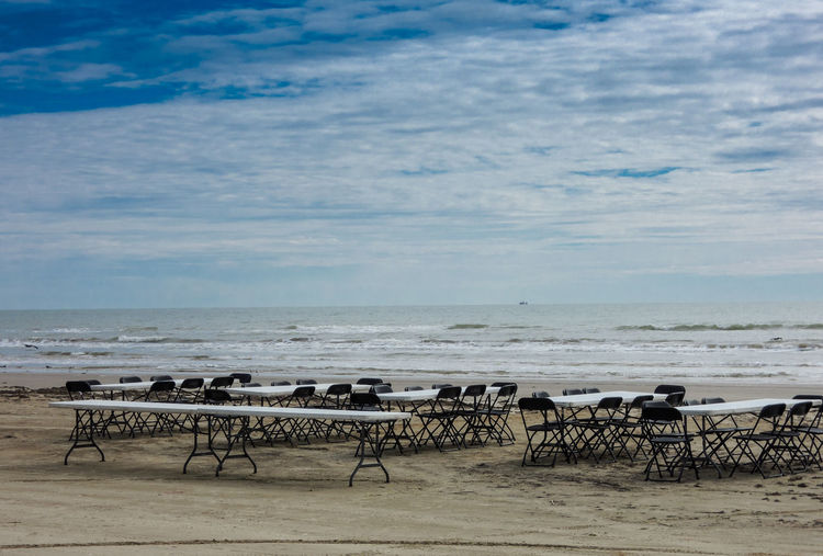 Tables and chairs arranged at beach against cloudy sky