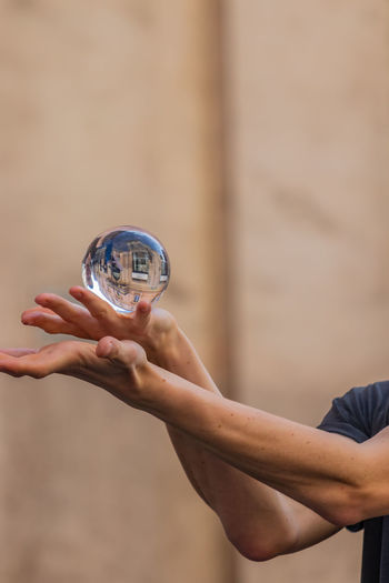 Close-up of hand holding crystal ball with reflection of building