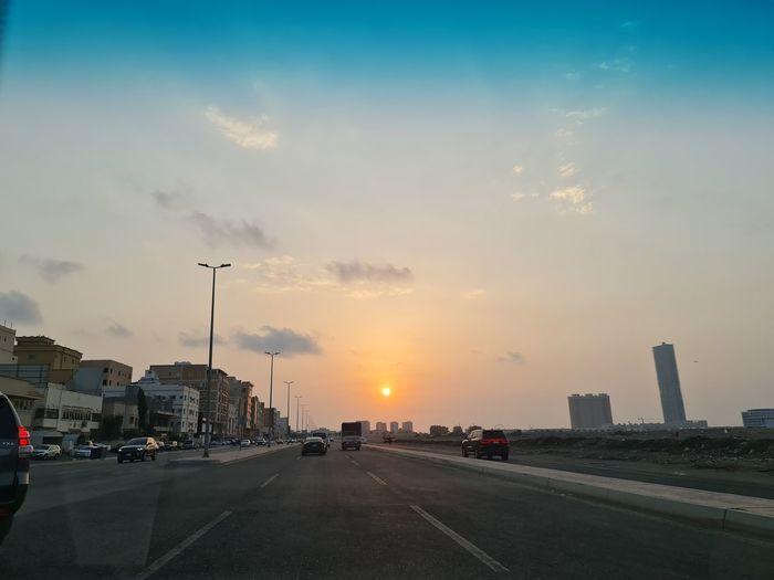 City street against sky during sunset