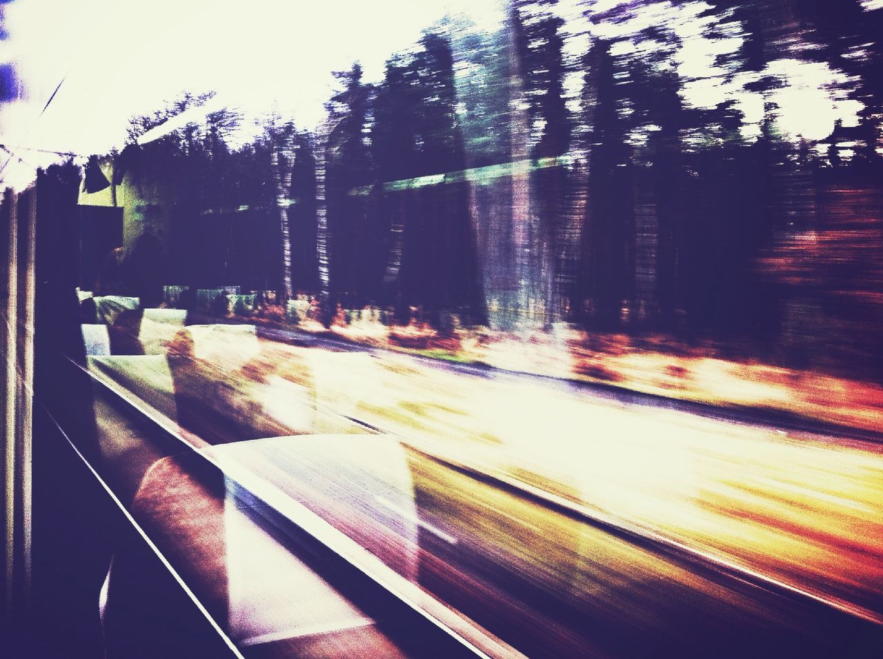 Blurred motion of trees and railroad tracks seen through train window