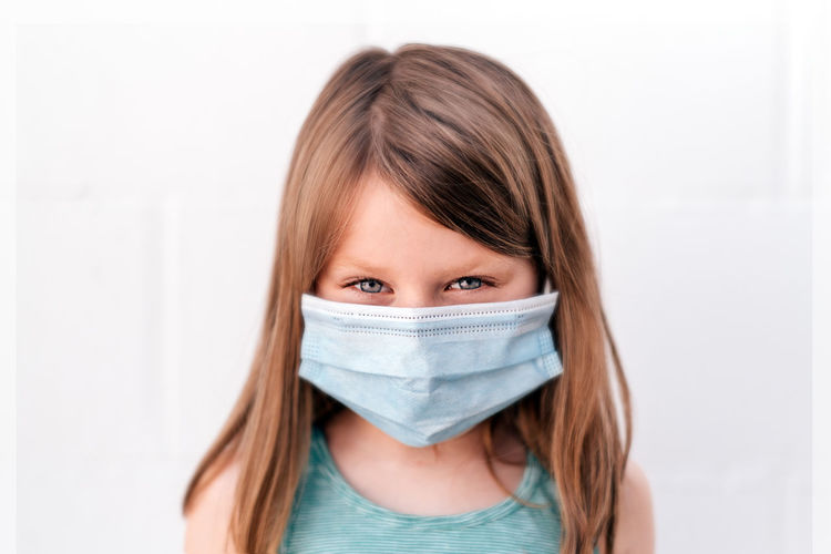 Portrait of a girl with blue eyes wearing an anti-virus mask with intese positive look
