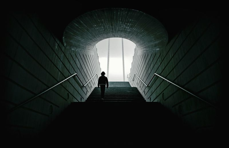 Low angle view of man walking on steps in tunnel