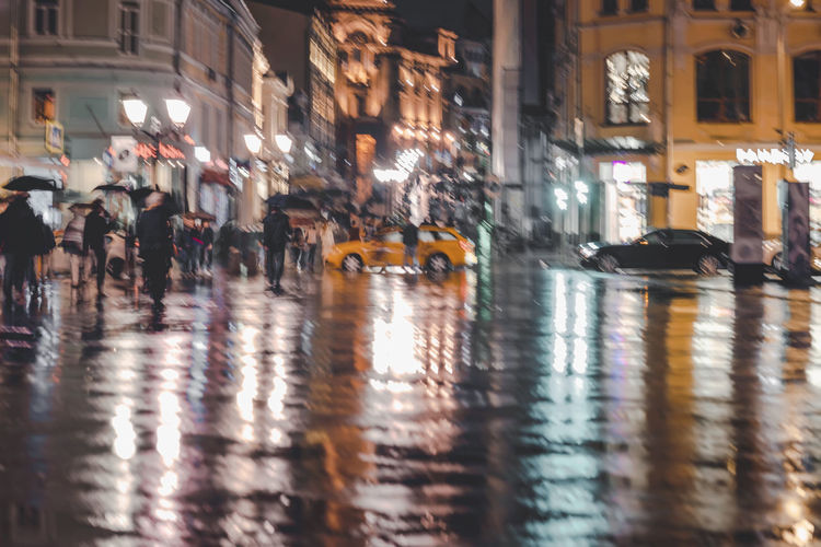 City street in rainy late evening, abstract background of blurred people figures under umbrellas. Intentional motion blur. Vivid colorful illumination from lanterns and shop windows Illuminated City Night Motion City Rainy Rain Blurred Motion Blur Abstract Evening Street Bright People Reflection Lamps Pavement Umbrella Transportation Architecture Car Outdoors Rainy Season Road City Life Group Of People Water City Street Motor Vehicle