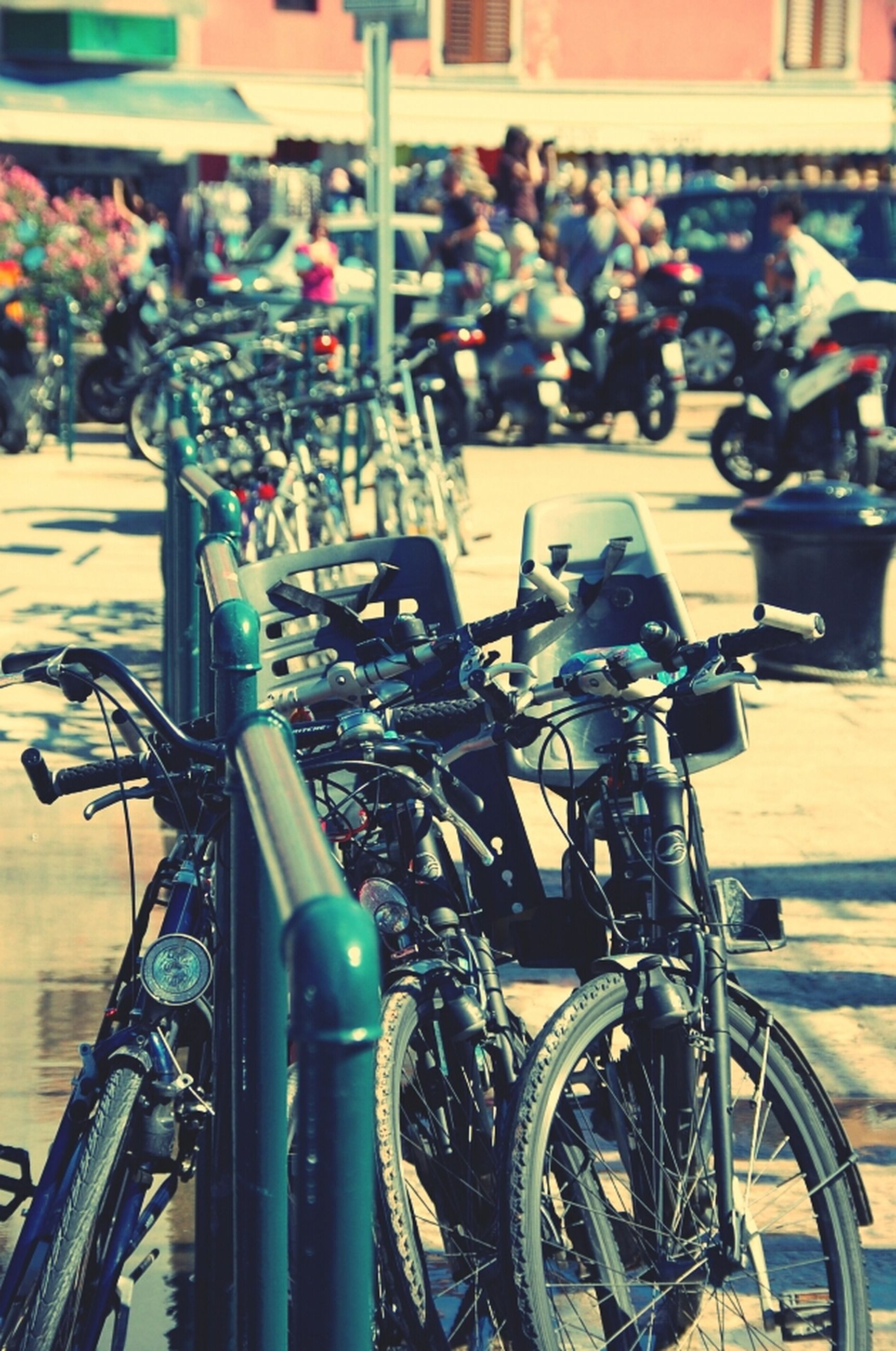 bicycle, land vehicle, transportation, mode of transport, building exterior, street, city, parked, stationary, architecture, built structure, parking, incidental people, car, city life, travel, city street, day, outdoors, focus on foreground
