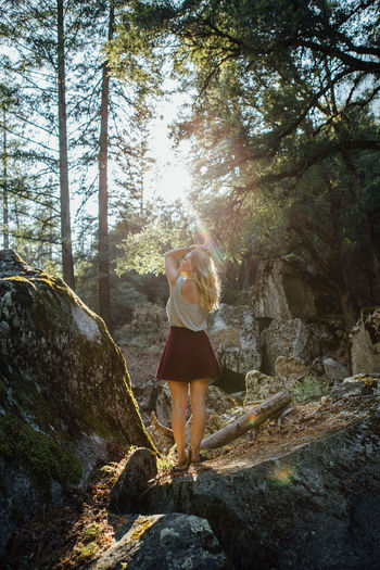 Rear view of young woman standing on rock in forest