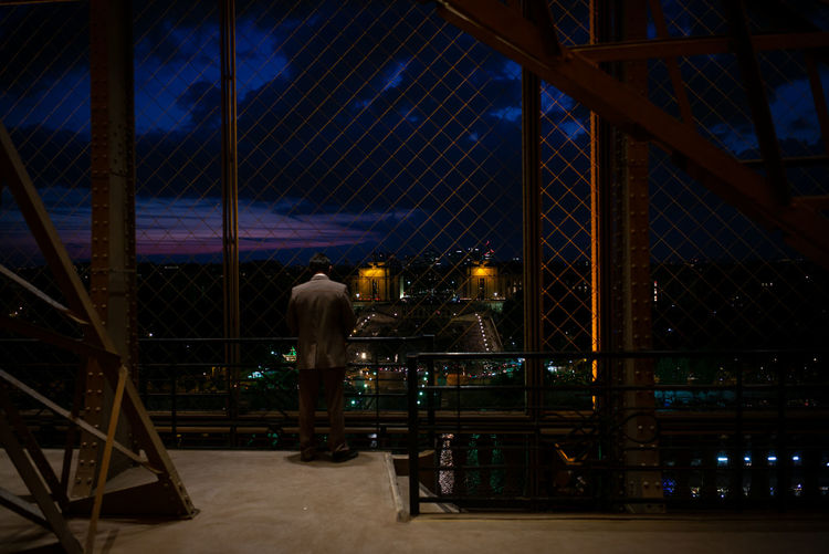 Rear view of man looking at city through fence at night