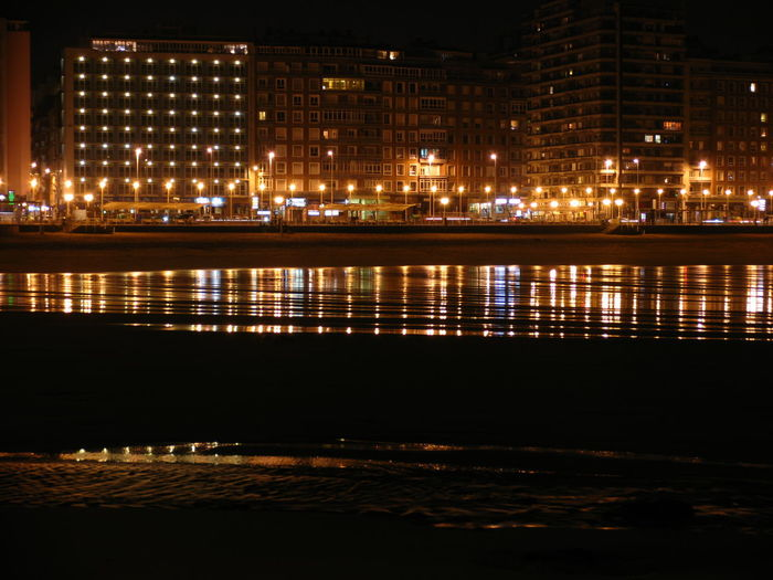 Illuminated buildings by beach against sky at night