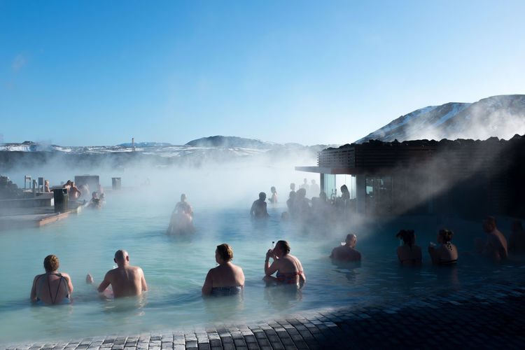 People Resting In Hot Spring Against Clear Blue Sky