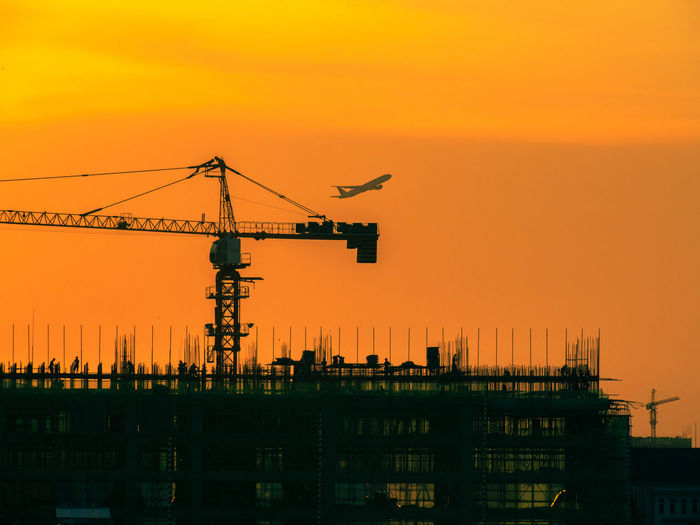 Cranes at construction site against sky during sunset