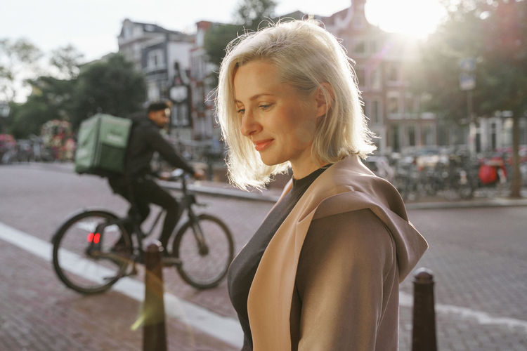 Young woman with bicycle on street in city