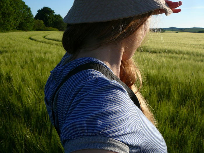 Close-up of woman wearing hat and shielding eyes while standing on land