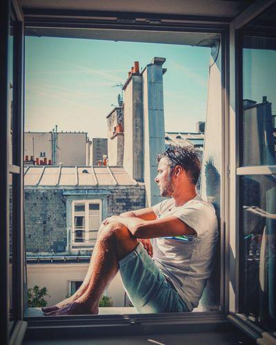 Man sitting on window sill in city