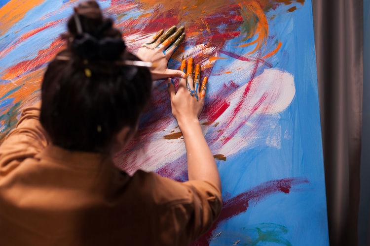 Rear view of woman against graffiti wall