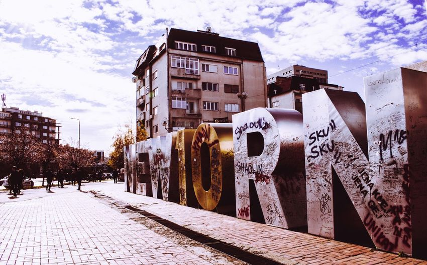 Graffiti on building by street against sky in city