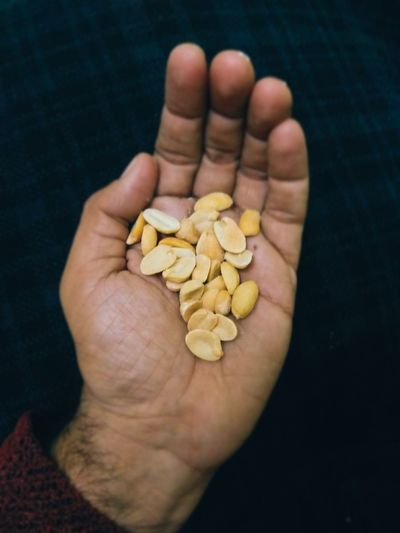 Cropped hand holding peanuts against black background