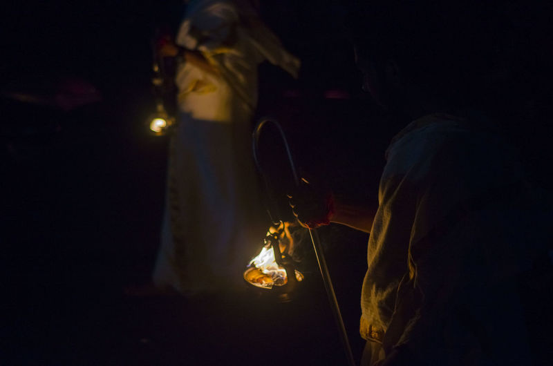 People carrying burning containers at night