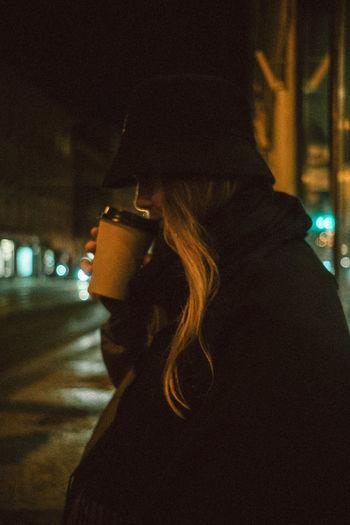 Rear view of woman on illuminated street at night