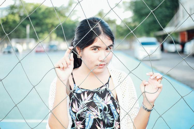 Portrait of woman seen through net in court
