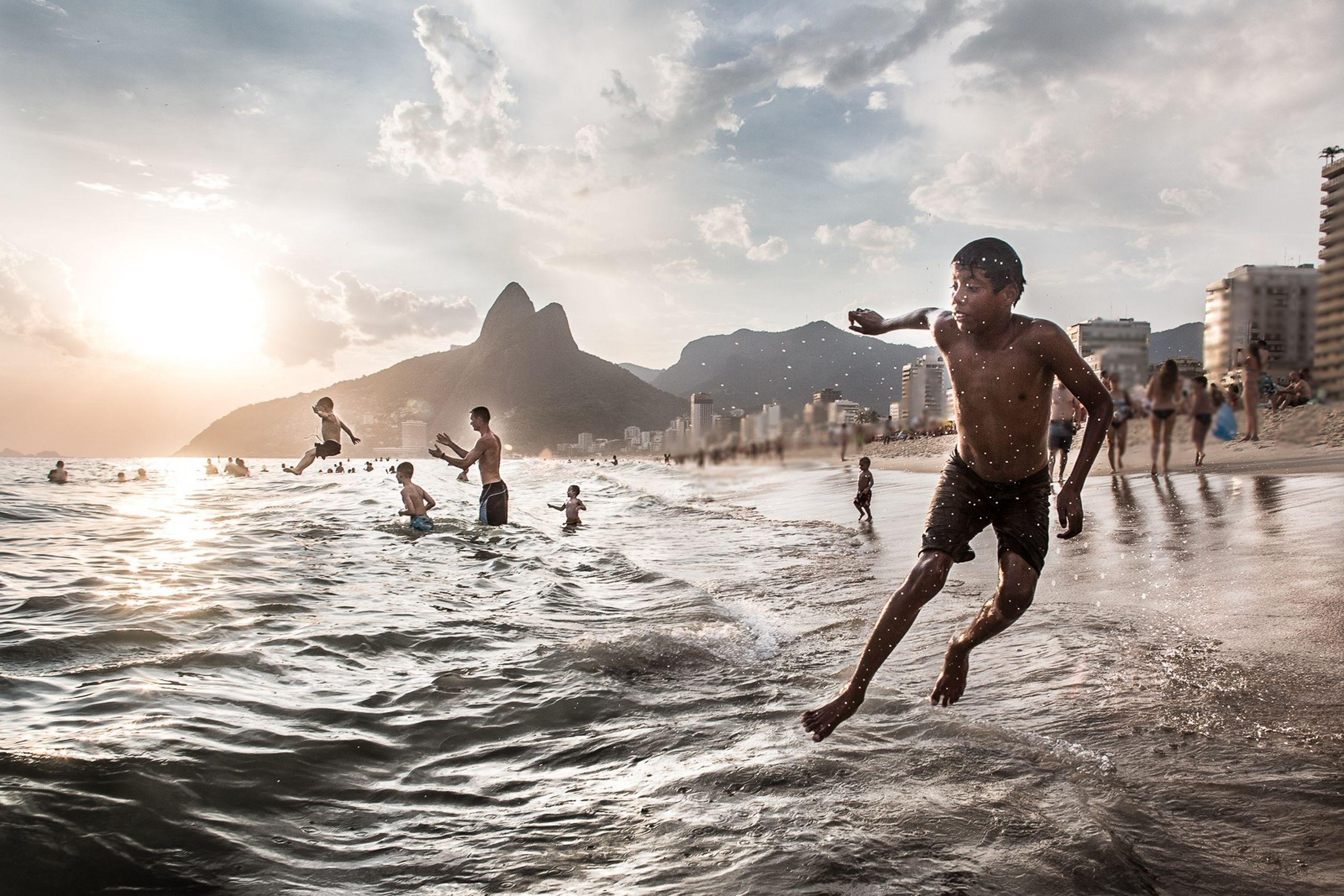 water, lifestyles, leisure activity, sea, sky, vacations, men, beach, enjoyment, full length, sunlight, waterfront, cloud - sky, tourist, wave, fun, weekend activities, travel