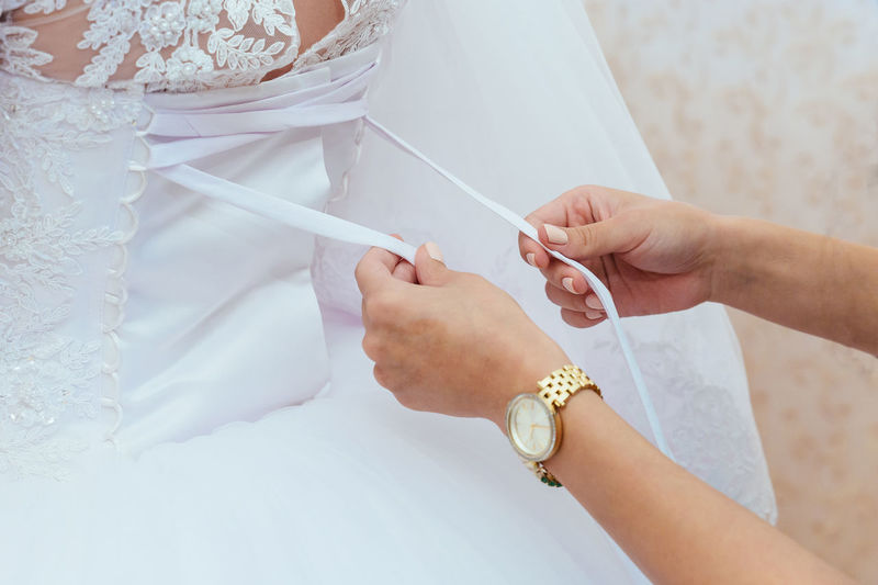 Close-up of hands assisting bride