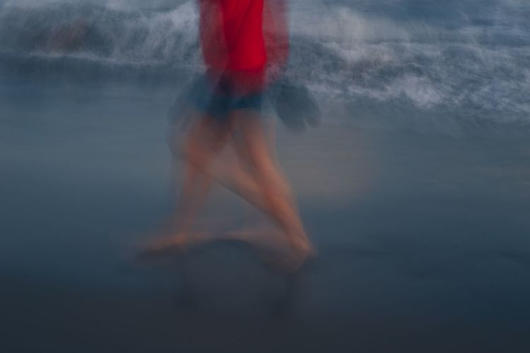 Blurred motion of woman standing in sea