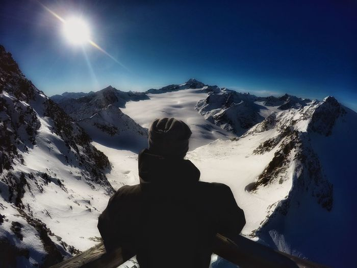Rear view of man standing at observation point against snowcapped mountains