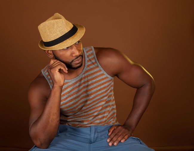 Man Wearing Hat Against Brown Background