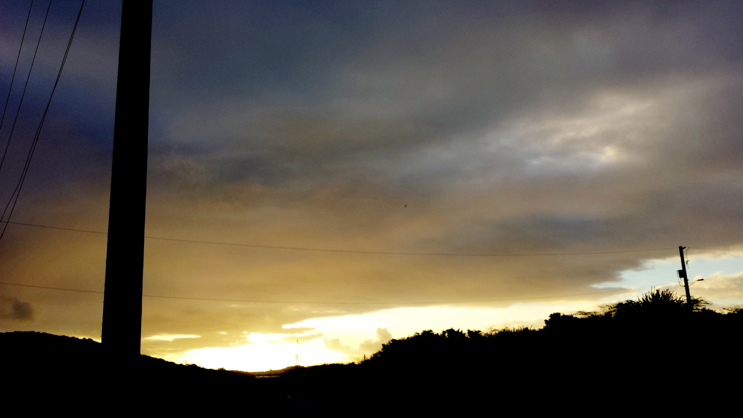 sunset, silhouette, sky, power line, electricity pylon, cloud - sky, low angle view, electricity, power supply, beauty in nature, scenics, tranquility, cloud, orange color, cable, nature, cloudy, tranquil scene, dramatic sky, connection