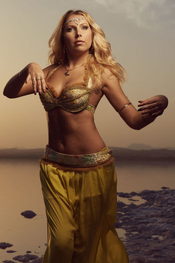 Beautiful blonde belly dancer woman on a lake in the evening. Golden colors Belly Dance Dancing Standing Beautiful Woman Beauty In Nature Belly Dancer Belly Dancing Caucasian Costume Evening Golden Color Lake Movement Nature One Person Outdoors Pose Real People Sky Standing Sunset Water Women Young Adult Young Women