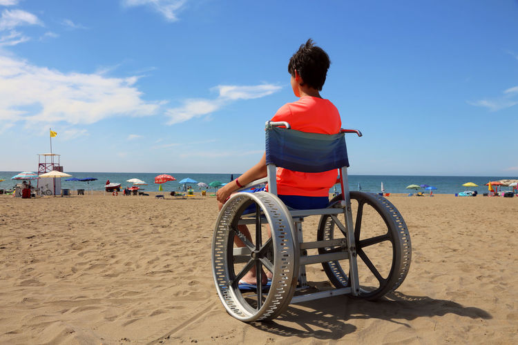 Young boy on the special wheelchair on the sand of beach in summer