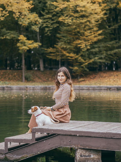 Woman sitting on bench by lake