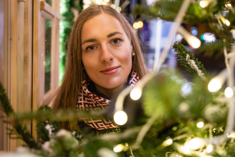 Portrait of young woman with christmas tree