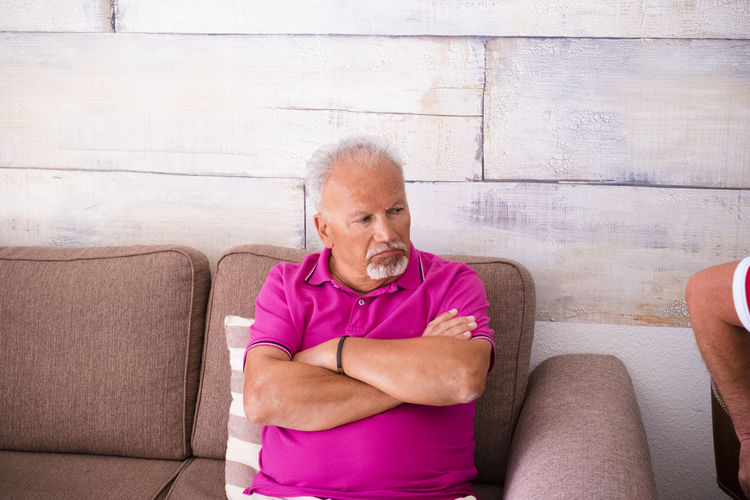 Senior Man Sitting On Sofa Against Wall At Home