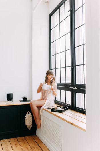 A beautiful girl in pajamas prepares breakfast and pours coffee near the window of the house