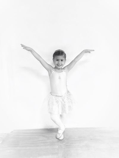 Portrait Of Smiling Girl Doing Ballet Dance Against Wall