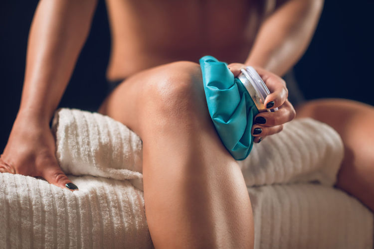 Midsection Of Woman Holding Ice Pack On Knee At Home