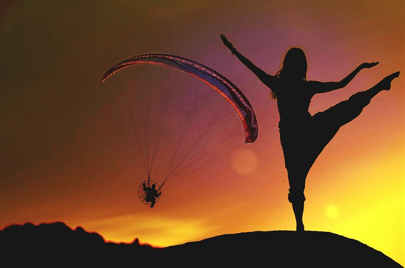 Woman performing yoga on cliff against paraglider in orange sky