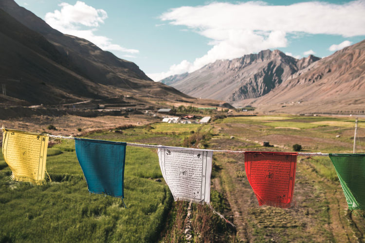 Clothes drying on field against mountains