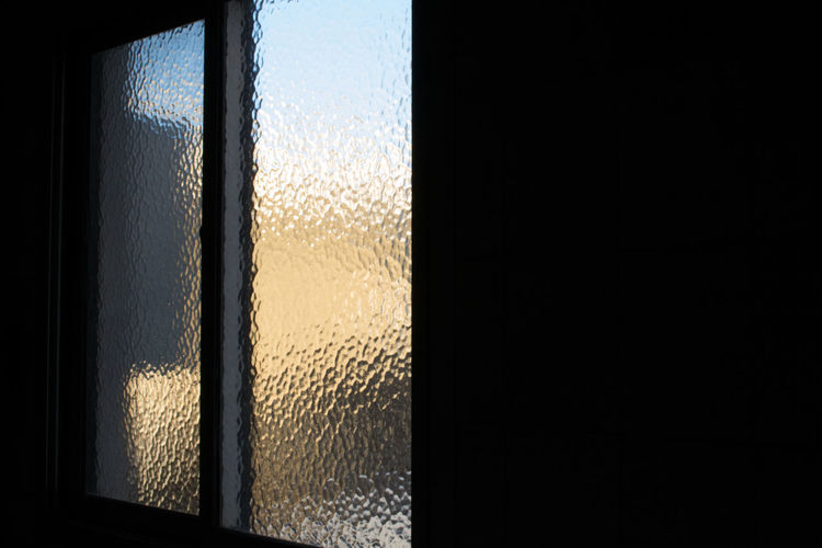 Close-up of glass window against wall