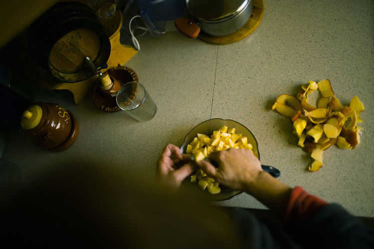 Cropped Hands Of Woman Cutting Apple In Bowl At Home
