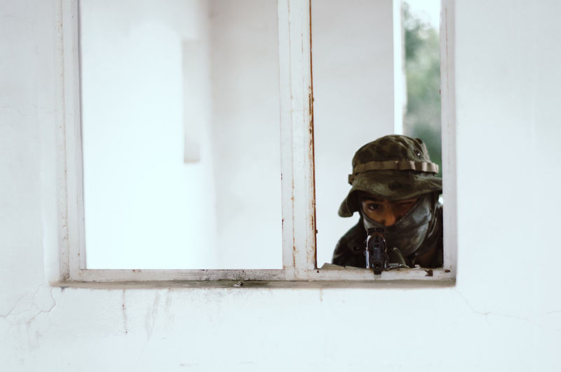 Special forces soldier holding rifle gun aim window white frame cover Window Day Helmet Security Portrait Indoors  Safety Architecture People Military Headwear Glass - Material Protection Real People Gun Built Structure Reflection Uniform Government Airsoft Sniper Trooper Soldier Army Army Soldier Special Forces Aim Aiming Camouflage Clothing Camouflage Hat AK 47 Gun