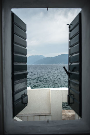 Scenic view of sea against sky seen through open window