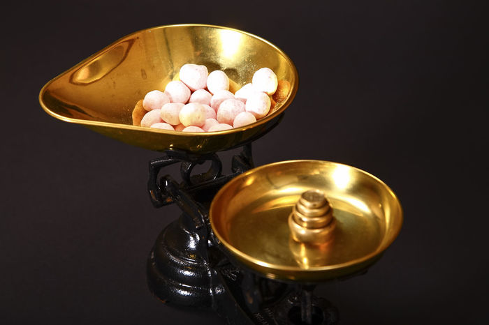 Sweets being weighed in vintage scales isolated on a black background Diet Old-fashioned Retro Sugar Sweet Tooth Weighing Scale Calorie Calories Candy Close-up Dieting Dieting Concept Gold Colored No People Old Scales Sweet Sweet Shop Sweets Treat Unhealthy Eating Vintage Vintage Scales Weighing Scales Weights