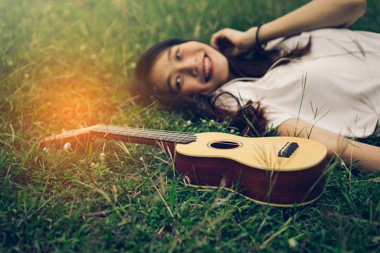 Smiling young woman listening music by ukulele on grass