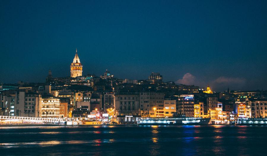 Sea by illuminated city at night