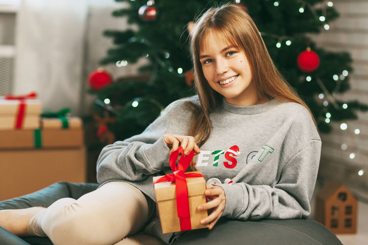 Beautiful teenage girl opens a gift made of kraft paper tied with a red ribbon